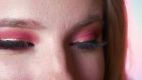 Closeup av att bedöva kvinnlig makeup för blåa ögon med rosa skuggor och guld- eyeline Slapp fokus Ögon som ser raka på lager videofilmer