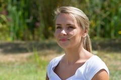 Closeup av att le den blonda flickan för 20-tal som tycker om solljus Royaltyfria Foton