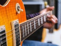 Closeup av att spela den elektriska gitarren Fotografering för Bildbyråer