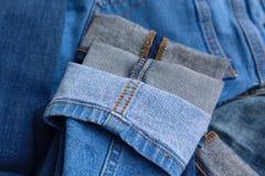 Closeup av att sy i manschetter av blå grov bomullstvilljeans i variation av färger arkivfoton
