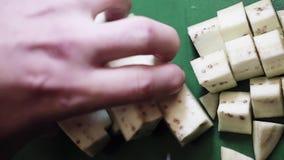 Closeup av aubergine som klipps in i kuber med den stora kniven på det gröna köksbordet lager videofilmer