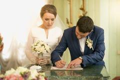Closeup av avtalet för bröllop för barnbrudgum det undertecknande på registreringsoffien Royaltyfri Bild