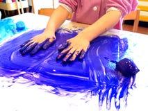 Closeup av barnhänder som målar under en skolaaktivitet - ismålning - som lär vid att göra, utbildning och konst, konstterapi royaltyfria foton
