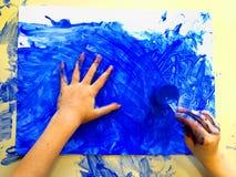 Closeup av barnhänder som målar under en skolaaktivitet - ismålning - som lär vid att göra, utbildning och konst, konstterapi arkivfoto