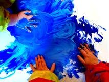 Closeup av barnhänder som målar under en skolaaktivitet - lära vid att göra, utbildning och konst, konstterapibegrepp royaltyfria bilder