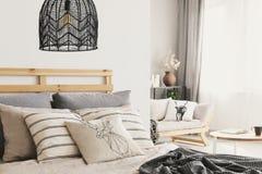 Closeup av bekväm säng med lotten av förbigick kuddar och varmt arkivfoto