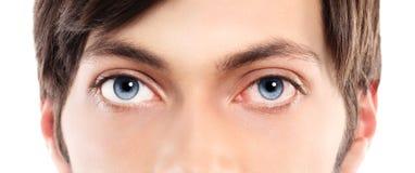 Closeup av blåa ögon från ung ett rött och irriterat öga för man med royaltyfria bilder