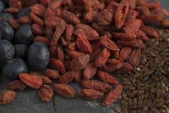 Closeup av blåbär, Goji och linfrö på stenyttersida Arkivfoton