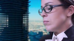 Closeup av brunetten i exponeringsglas Hon sitter i studion i en affärsdräkt och maskinskrivning på hennes minnestavla stock video