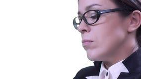 Closeup av brunetten i exponeringsglas Hon sitter i studion i en affärsdräkt och maskinskrivning på hennes minnestavla lager videofilmer