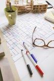 Closeup av byggnadsmodell- och skissninghjälpmedel på ett konstruktionsplan. Arkivbild