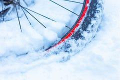Closeup av cykelkedjan, hjul med eker som ligger i snö royaltyfria foton