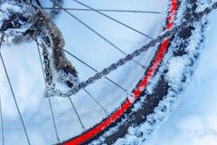 Closeup av cykelkedjan, hjul med eker som ligger i snö royaltyfri fotografi