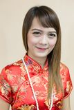 Closeup av den asiatiska kvinnahälsningen i traditionell kines eller cheongsam med pärlan i kinesisk beröm för nytt år royaltyfri bild