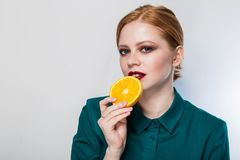 Closeup av den attraktiva älskvärda unga kvinnan som äter apelsinen på vit bakgrund arkivfoton