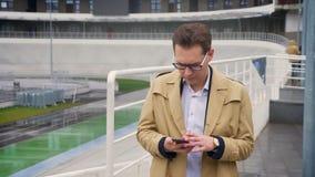 Closeup av den attraktiva caucasian mannen som ut tar facket hans telefon och får spännande över goda nyheter utomhus i lager videofilmer