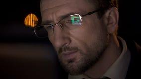 Closeup av den detektiv- framsidan, manlig seende PCskärm reflekterad i hans glasögon arkivfoto