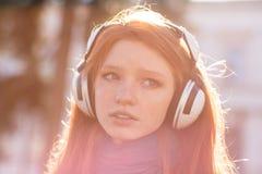 Closeup av den fundersamma nätta unga damen i hörlurar royaltyfri fotografi