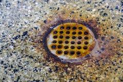Closeup av den gamla våta och rostade runda räkningen för metallgolvavrinning Royaltyfri Foto