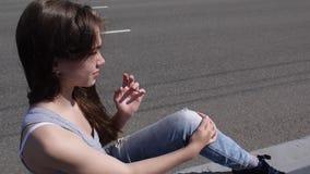 Closeup av den gulliga caucasian tonåriga flickan på en stadsbakgrund Ser in i avståndet Statisk kamera arkivfilmer