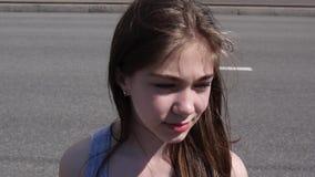 Closeup av den gulliga caucasian tonåriga flickan på en stadsbakgrund Ser in i avståndet Statisk kamera stock video