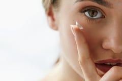 Closeup av den härliga kvinnan som applicerar ögat Lens i öga arkivbilder