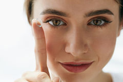 Closeup av den härliga kvinnan som applicerar ögat Lens i öga royaltyfria bilder