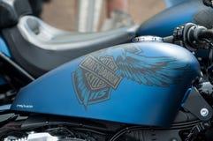 Closeup av den Harley Davidson logoen på den blåa mopedbehållaren av den Harley Davidson mopeden som parkeras i gatan Arkivfoto