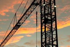 Closeup av den industriella kranen på solnedgången royaltyfri bild