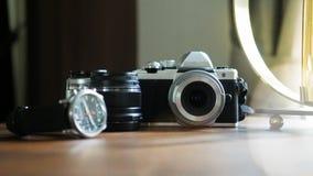 Closeup av den klassiska kameran på ett träskrivbord med den utvalda fokusen för armbandsur- och linsutrustning Bakgrund med ett  royaltyfria foton