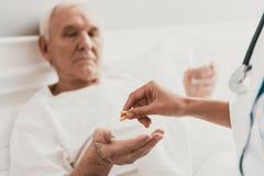 Closeup av den kvinnliga doktorn som ger preventivpillerar till patienten royaltyfri foto