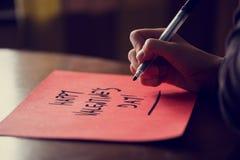 Closeup av den kvinnliga handen som skriver lyckligt valentin daguttryck på r Arkivbild