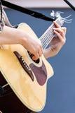 Closeup av den kvinnliga musikern som spelar den akustiska gitarren arkivbild