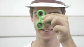 Closeup av den lyckliga tonårs- pojken som vrider och spelar med yttersidan för rastlös människaspinnareleksak - arkivfilmer