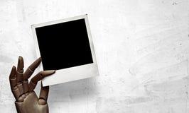 Closeup av den mörka wood handen med polaroidramen Arkivfoton