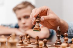 Closeup av den manliga handen som rymmer ett schackstycke över a Royaltyfri Foto