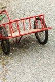Closeup av den röda arbeta i trädgården spårvagnen med stora hjul Royaltyfria Bilder