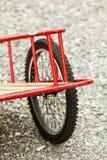 Closeup av den röda arbeta i trädgården spårvagnen med stora hjul Arkivfoto