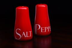 Closeup av den röda salt-källaren och peppar-ask på mörk bakgrund av Cristina Arpentina Royaltyfri Bild