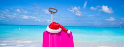Closeup av den rosa resväskan och den Santa Claus hatten på Arkivfoto