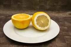 Closeup av den skivade citronen och apelsinen i den vita plattan Royaltyfria Bilder