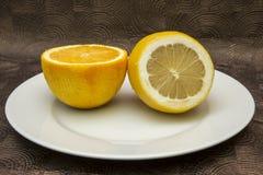Closeup av den skivade citronen och apelsinen i den vita plattan Arkivfoto
