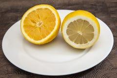 Closeup av den skivade citronen och apelsinen i den vita plattan Fotografering för Bildbyråer