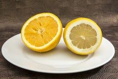 Closeup av den skivade citronen och apelsinen i den vita plattan Royaltyfri Bild