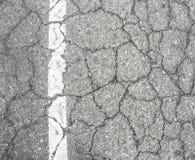 Closeup av den spruckna asfaltvägen Fotografering för Bildbyråer
