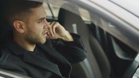 Closeup av den stressade svära och talande telefonen för affärsman, medan sitta inom bilen utomhus stock video