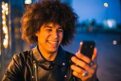 Closeup av den unga afro amerikanska grabben som använder den smarta telefonen i gatan på natten royaltyfri fotografi