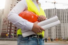 Closeup av den unga arkitekten som poserar med hardhaten och ritningar på Arkivfoto