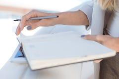 Closeup av den unga blonda affärskvinnan som tar anmärkningar arkivfoton