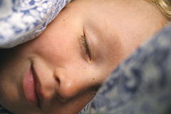 Closeup av den unga caucasian pojken som sover under räkningar Royaltyfria Bilder